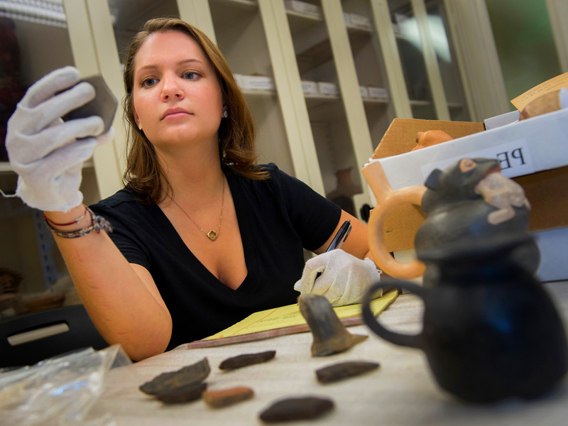 A young woman studies an old piece of pottery in a lab.